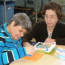 Michelle Bourgeois working on a craft project with Eve Corning.
