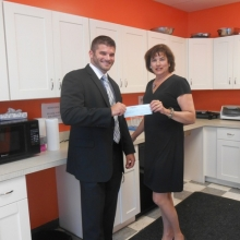 David Felton, Vice President and Senior Business Banking Officer at Rockland Trust, presents a check for $10,000 to Roslynn Rubin, GWArc CEO, in GWArc's updated kitchen at 56 Chestnut Street, Waltham. The Rockland Trust Charitable Foundation granted the funds to support recently completed upgrades to GWArc's kitchen and a program room to improve safety and increase space for program activities. While GWArc continues to seek larger community space, these critical updates allow the agency to maintain quality programs and services.