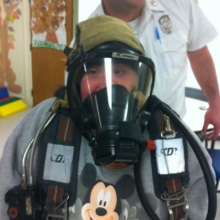 Ellen Pictour tries on fire safety gear at a Watch City Self Advocates meeting.