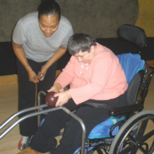Cindy DeLeo tries adaptive bowling with Day Habilitation staff member Diana Lee.