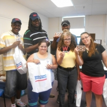 GSE participants and staff display items they received during a tour of Watertown Savings Bank.