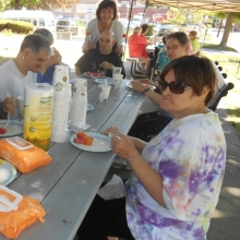 Day Education participants enjoy a summer cookout under the shady canopies.