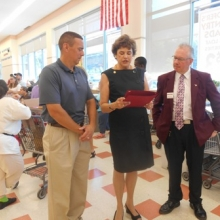 Roz Rubin reads a proclamation from Waltham Mayor Jeannette McCarthy in recognition of the Rotary-GWArc Day of Service for Waltham Food Pantries while Dan Messina, Waltham Rotary Club President (left) and Mike Dunleavy, Waltham Market Basket Manager, look on.