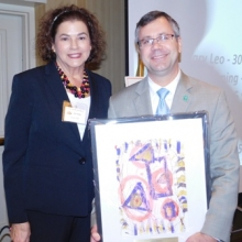 Charles Botto, Embassy Suites General Manager, accepts a thank you gift of an Artists of GWArc painting.
