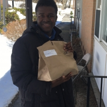 Alex N. delivers a Meals on Wheels lunch to a senior citizen in Waltham.