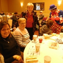 Mayor Jeannette McCarthy (standing) enjoys visiting with friends at Harvest Breakfast.