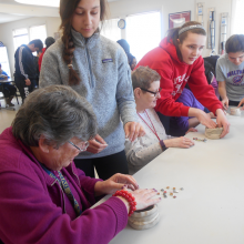 Students and CBDS participants work together to create and decorate clay bowls.