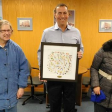 Dan Messina of Hillcrest Properties displays an Artists of GWArc painting delivered to his office by Day Hab participants Mary Ann M. (left) and Michelle B (right).