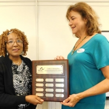 Rhonda Fleming holds the John L. Battaglino Award of  Excellence plaque that lists 2017 and past awardees with Roz Rubin, GWArc CEO.