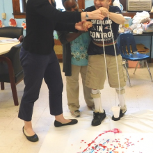 Carolyn Melbye, art therapist with ARTrelief (left) and Tanya Brown, DD Assistant (center) assist Tommy R. to add his touch to a painting by dripping paint.
