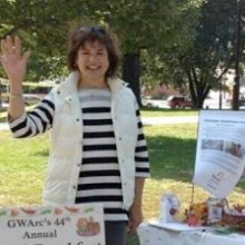 CEO Roz Rubin waves from GWArc's Table at Waltham Day on the common