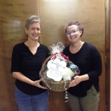 Leah Igdalsky presents Debora Hoffman with a basket of BARK @ GWArc to be used as a raffle prize at REACH Beyond Domestic Violence's Fall Festival.